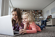 Two little sisters lying on the floor at living room with laptop while her parents sitting in the background - RBF003399
