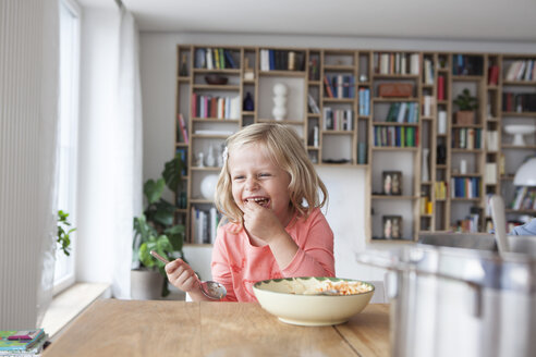 Portrait of laughing little girl eating spaghetti - RBF003414