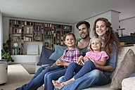 Family portrait of couple with two little girls sitting together on couch in the living room - RBF003416