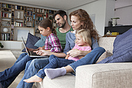 Couple sitting with their with two little daughters on couch in the living room looking at laptop - RBF003418