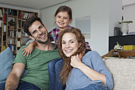 Portrait of happy couple and little daughter on the couch at home - RBF003423