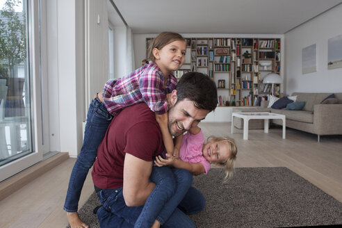 Man playing with his little daughters  in the living room - RBF003429