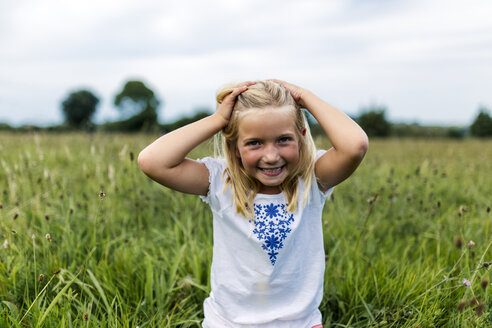 Portrait of smiling girl with hands in her hair on a meadow - MGOF000501