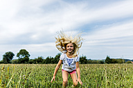 Portrait of girl jumping in the air on a meadow - MGOF000504