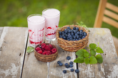 Raspberry milkshake in glasses, blueberries and raspberries - KSWF001550