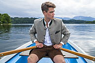 Germany, Bavaria, young man rowing on Staffelsee - TCF004852