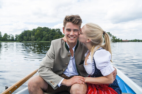 Germany, Bavaria, young couple sitting in a rowing boat on Staffelsee - TCF004857