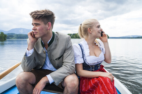 Germany, Bavaria, young couple wearing traditional clothes sitting in a rowing boat on Staffelsee - TCF004864