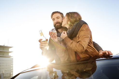 Happy couple looking through sunroof of a car sharing a scarf - PESF000166