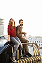 Happy couple sitting on car roof - PESF000170