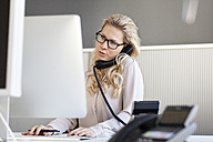 Blond woman in office on the phone - PESF000072