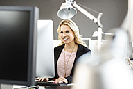 Smiling blond woman working at desk in office - PESF000106