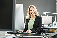 Smiling blond woman working at desk in office - PESF000109