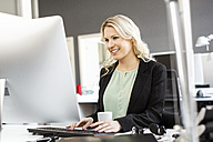 Smiling blond woman working at desk in office - PESF000110