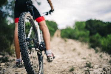Spain, Tarragona, Mountain biker in extreme terrain, low section, rear view - JRFF000013