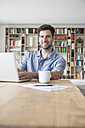 Portrait of smiling man at home using laptop - RBF003558