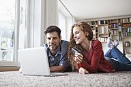 Happy couple lying on floor shopping online - RBF003519