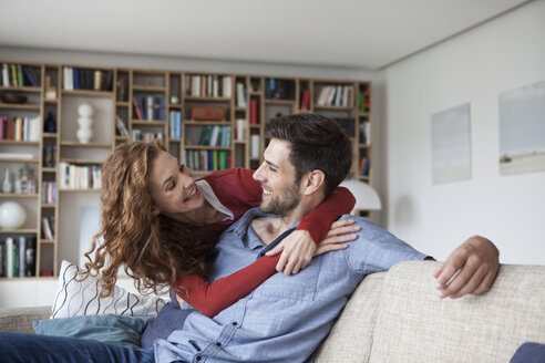 Happy woman hugging man on couch - RBF003530