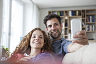 Relaxed couple at home on couch looking on cell phone - RBF003559