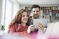 Relaxed couple at home on couch using digital tablet - RBF003536
