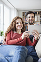 Relaxed couple at home on couch using digital tablet - RBF003537