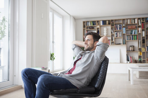 Smiling man at home sitting in armchair with hands behind head - RBF003563