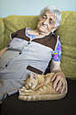 Tabby kitten snoozing besides old woman on the couch at home - RAEF000377
