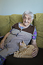 Portrait of senior woman sitting on couch with tabby kitten - RAEF000379