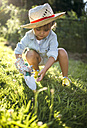 Little girl crouching with gardening glove and hand trowel on a meadow - MGOF000512