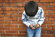 Head of little boy leaning on brick wall looking down - MGOF000529