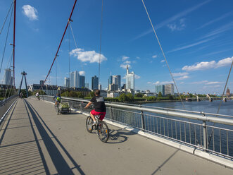 Germany, Hesse, Frankfurt, Financial district, cyclists on Holbeinsteg bridge over Main river - AM004150