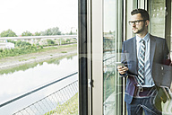 Young businessman with cell phone looking out of window - UUF005410