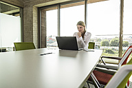 Young businesswoman in conference room using laptop - UUF005444