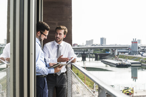 Two young businessmen with documents and digital tablet discussing on balcony - UUF005468