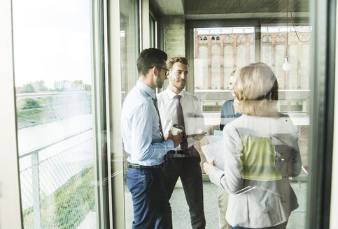 Business people with documents talking at the window - UUF005511