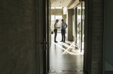 Two businessmen standing in office hall - UUF005534