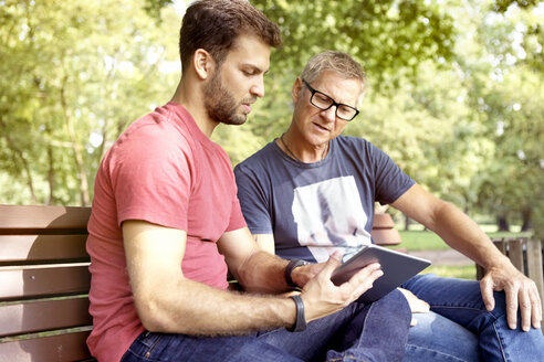 Two men sitting on a park bench looking at digital tablet - SEGF000414