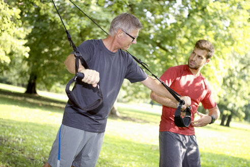 Man doing TRX training while his personal trainer watching him - SEGF000399