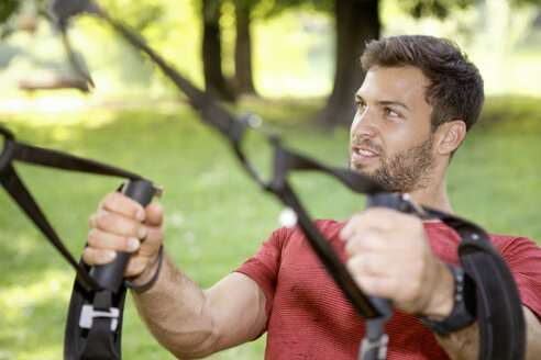 Portrait of sportive man doing TRX training in a park - SEGF000401