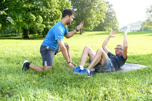 Man doing strength training on a meadow while his personal trainer watching him - SEGF000418