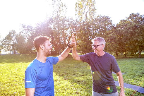 Personal trainer giving client high five after training in a park - SEGF000411