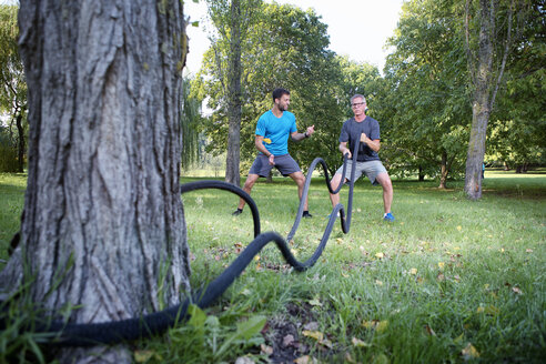 Man training with battle rope while his personal trainer watching him - SEGF000412
