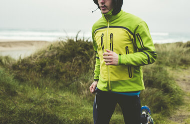 Spain, Valdovino, young man jogging on the beach at rainy day - RAEF000387