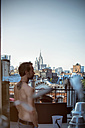 USA, New York City, Man standing on rooftop terrace, looking view - ONF000860