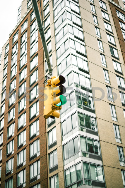 USA, New York City, Green traffic light in front of high rise buidling - ONF000871