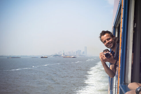 USA, New York City, Tourist with camera on Staten Island Ferry with view of Manhattan skyline and East River - ONF000921