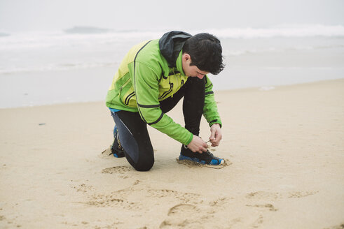 Spain, Valdovino, young man tying his shoe on the beach at rainy day - RAEF000398
