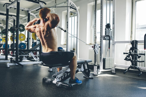 Physical athlete exercising with cable machine - MADF000581