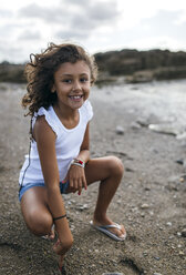 Spain, Gijon, portrait of smiling little girl crouching on the beach - MGOF000537