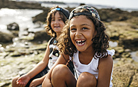 Spain, Gijon, portrait of laughing little girl and her friend in the background sitting at rocky coast - MGOF000543